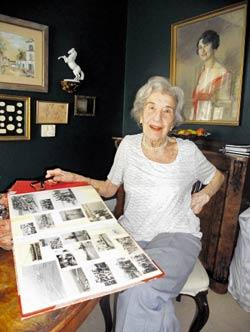 Anne Pisker in ihrem Wohnzimmer. Auf dem Tisch liegt ein Album mit Schwimmfotos aus den 30ern, an der Wand hängt das eine Bild ihrer Mutter, das sie einem großen Zufall verdankt.