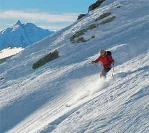 Tiefschneeabfahrt mit Blick auf den Großglockner: Rund um Heiligenblutlockt vor allem abseits der Pisten der g'führige Schnee. Foto: Klaus Dapra/Tiscover