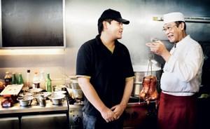 Meisterkoch Xiao Liu Sheng (mit lackierter Ente) und sein Sohn Xiao Peng in der winzigen Küche ihres Restaurants in der Wiener City.