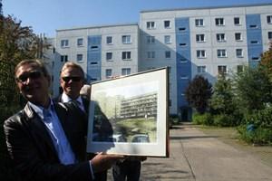 2004 wurden die Wohnblöcke komplett saniert. Die meisten Wohnungen verfügen heute über einen 6 m² großen Balkon. (Bild: Vertreter der Firma Hausinvest zeigen den Block, wie er vor der Sanierung aussah.)