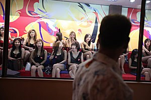 """Schaufenster der Lust: Ein Kunde vor Thai-Prostituierten in """"Whores' Glory""""."""