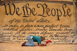 Artikelbild: Protestalltag  in New York: Ein Wall-Street-Besetzer setzt seine Unterschrift auf eine  riesige  Kopie der  amerikanischen  Verfassung. - Foto: AFP/Samad