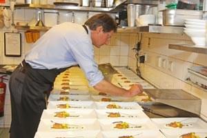 Klubobmann Bucher beim Beträufeln seines Lachsforellentatars mit Mangos und Weintrauben.