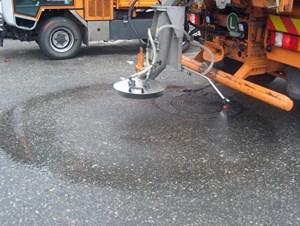 Mithilfe eines Schlauchs und einer Düse wird das Calcium-Magnesium-Acetat, ein flüssiges Gemsich aus Kalkstein und Essigsäure, auf die Straße aufgesprüht.