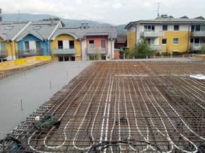 Dieses Bild zeigt, wie das Rohrleitungssystem für die bauteilaktivierte Betondecke im Gemeindezentrum Rif verlegt wird.