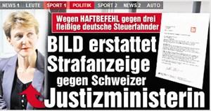 """Die Schweiz zeigt Flagge vor dem Reichstagsgebäude in Berlin (oben) - und mit ihrem Haftbefehl gegen deutsche Steuerbeamte, gegen den nun die """"Bild""""-Zeitung ihre Geschütze in Stellung bringt."""