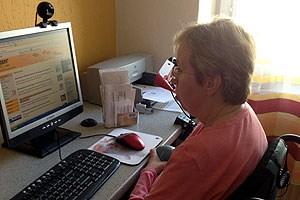 Karin Sieber an ihrem Computer. Sie surft im Internet mit ihrer Mundmaus.