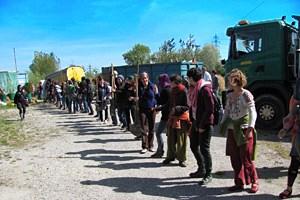 Eine Menschenkette befördert Pflanzen und Wekzeug aus dem geräumten Areal.