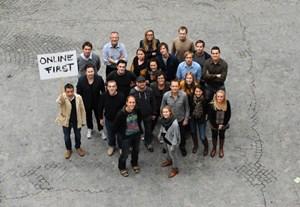 """Das junge Team demonstriert mittels selbst gemaltem Schild seine journalistische Geisteshaltung: """"Online First""""."""