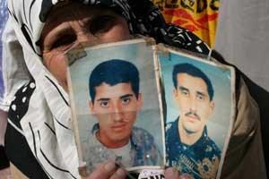 Mutter mit Bildern ihrer verschwundenen Söhne.