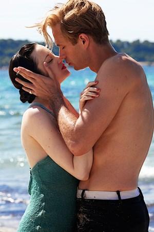Wallis Simpson (Andrea Riseborough) macht sich gut vor Meeresschaum und in den Armen des Thronfolgers (James D'Arcy).