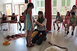 Damit die Kinder die Körpersprache der Hunde besser verstehen, schlüpfen sie selbst in die Rolle eines Tiers. Dazu bekommen sie einen Stoffschwanz umgebunden.