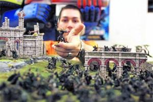 """Einer der Spieler im Games Workshop mit einer seiner Figuren aus """"Der Herr der Ringe"""" inmitten eines aufgebauten Schlachtfelds. Was aussieht wie völliges Chaos, ist die Ordnung des Spiels."""