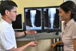 Oberarzt Rudolf Ganger erläutert einer Patientin den Fitbone. Auf dem Röntgenbild ist der implantierte Nagel im Bein zu sehen.