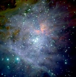 Im Infrarotbereich können Astronomen durch die Wolke sehen und die tausenden lichtschwachen Sterne des Haufens in ihrem Inneren sichtbar machen. Auf dieser Aufnahme der Europäischen Südsternwarte ist das sogenannte Trapez aus vier hellen Sternen im Zentrum besonders gut erkennbar. Zwischen ihnen würde sich das hypothetische Schwarze Loch befinden.