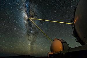 """Die beiden Spiegelteleskope des Keck-Observatoriums auf Hawaii fokussieren auf das Zentrum der Milchstraße. Mit Lasern wird ein """"künstlicher Stern"""" in der äußeren Erdatmosphäre erzeugt, um ein Maß für den Verzerrungseffekt der darunter liegenden Schichten zu finden."""
