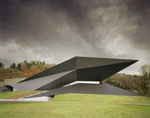 Das Wiener Büro DMAA setzte dem Altbau ein eckiges, kantiges Etwas zur Seite, das sich dynamisch aus dem Berg dreht. Die dunkelgraue Fassade weist ein ungewöhnliches Muster auf.
