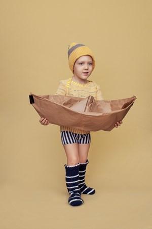 Carl mit DIY-Spielzeug aus Packpapier und Gaffa-Band, Haube und Socken sind selbstgetrickt.
