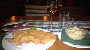 A meal of wiener schnitzel, potato salad and rosé wine at Mayer am Pfarrplatz.