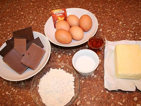 Zutaten:200 g Zartbitterschokolade100 g Milchschokolade250 g Butter4 EL Kristallzucker5 Eier1 Prise Salz1 Pkg. Vanillezucker100 g Mehl4 cl RumWaldbeeren (Tiefgekühlt)Cointreau
